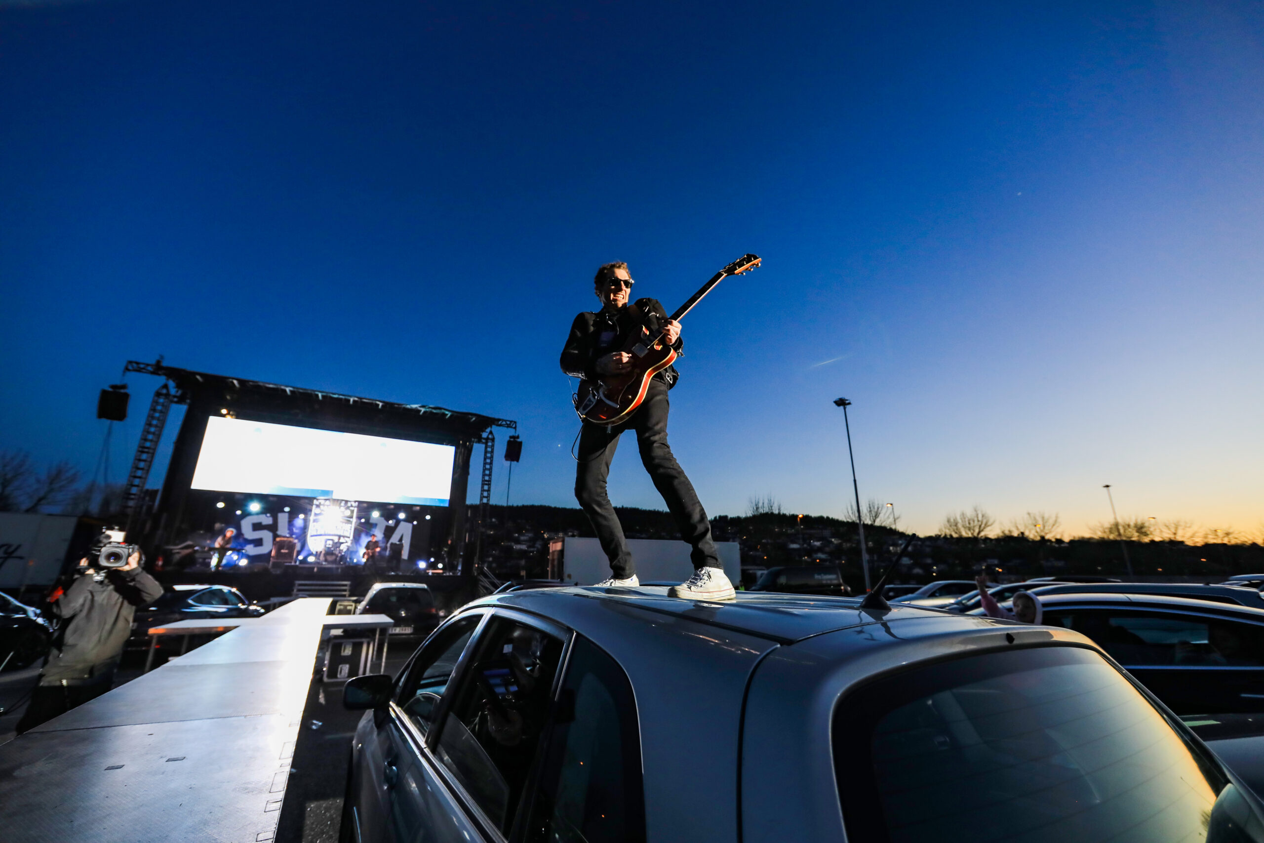 A guitarist on the roof of a car